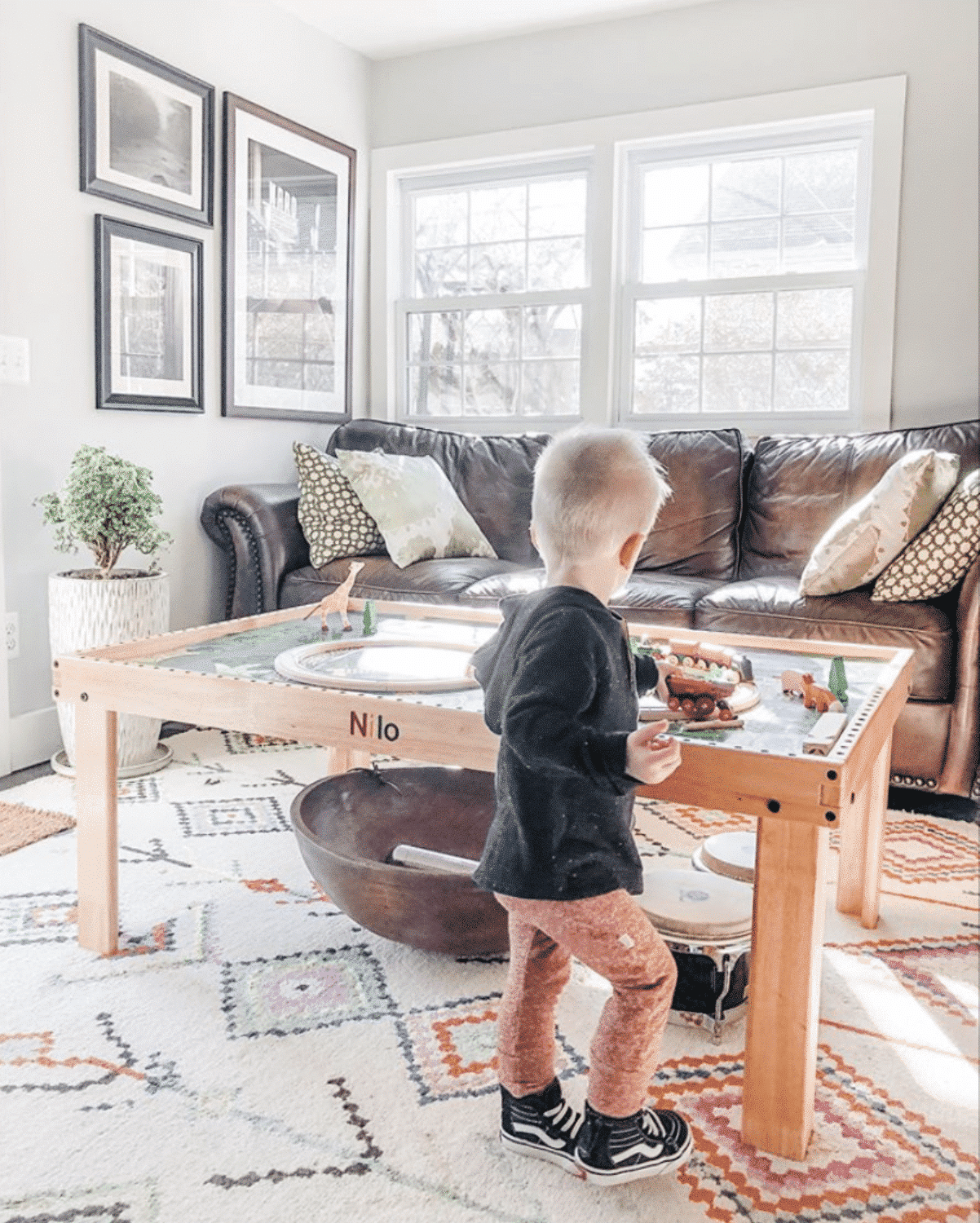 Toddler playing with toy train set on a Nilo childrens play table