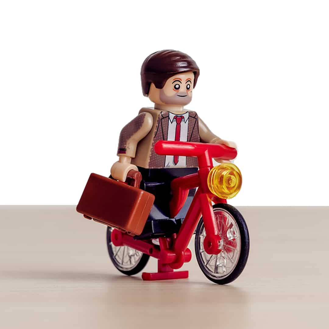 Adult Lego character biking towards the best lego table for adults